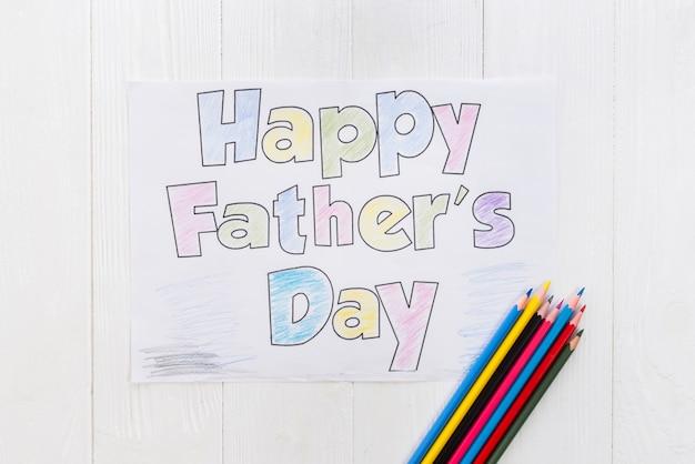 Inscripción del día de padres feliz con lápices en la mesa