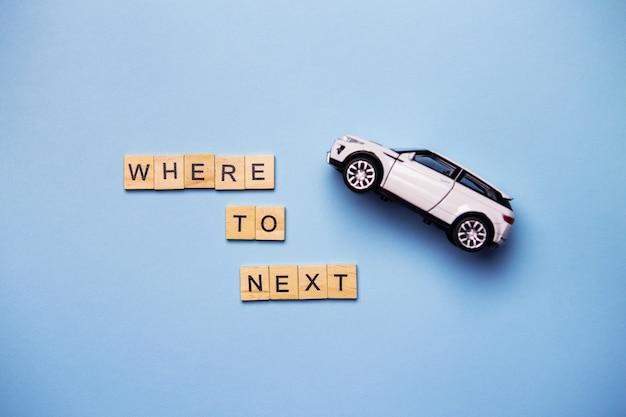 La inscripción dónde seguir las letras de madera en una pared azul, una vista superior. viaje automático con un automóvil blanco al costado de la carretera.