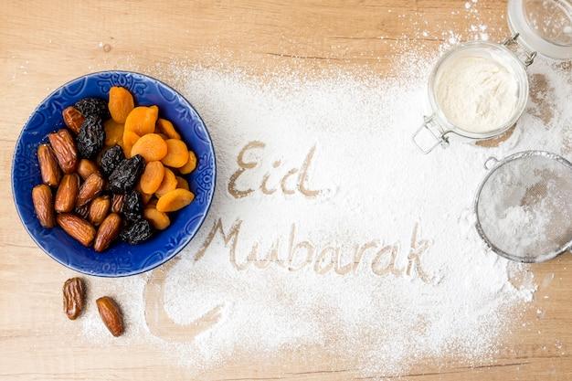 Inscripción de eid mubarak en harina junto a frutos secos.