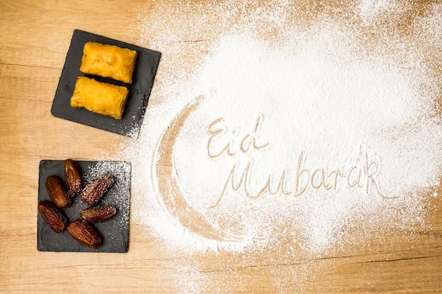 Inscripción de eid mubarak sobre harina con dulces del este.