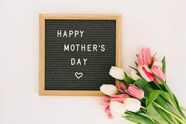 Inscripción feliz del día de madres a bordo con los tulipanes rosados