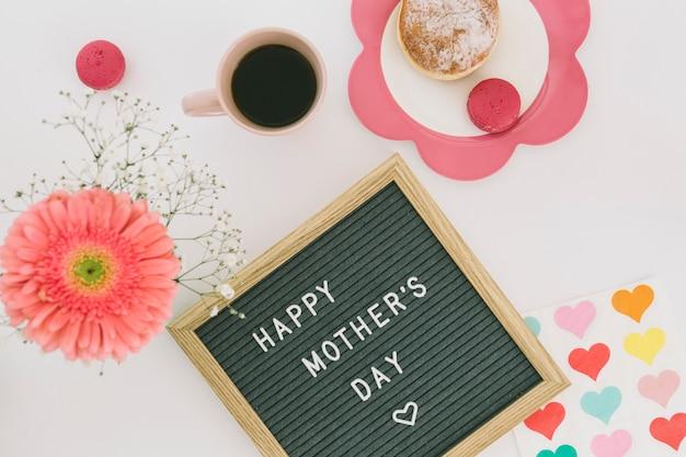 Inscripción de feliz dia de las madres con cafe y flor