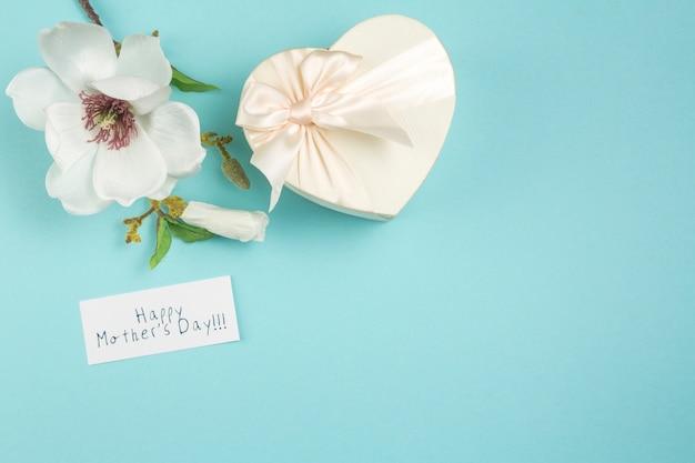 Inscripción de feliz dia de las madres con flor y regalo