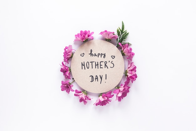 Inscripción feliz del día de madres con flores de color púrpura