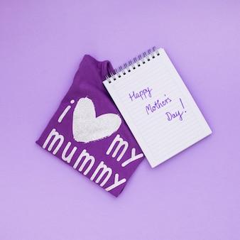 Inscripción feliz del día de madres en la libreta con la camiseta