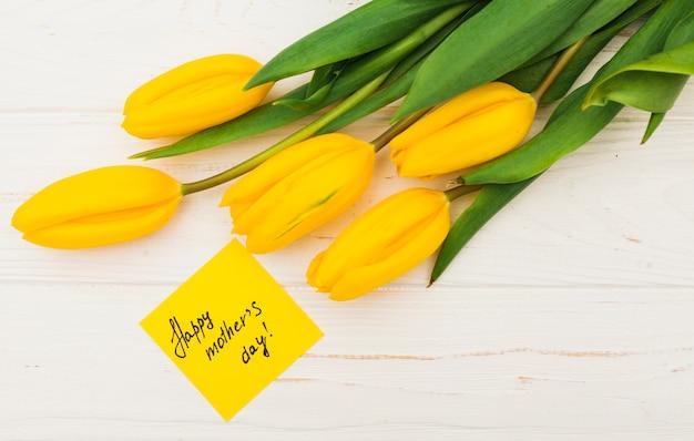 Inscripción de feliz día de las madres con tulipanes amarillos