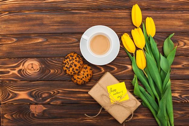 Inscripción de feliz día de las madres con tulipanes y café