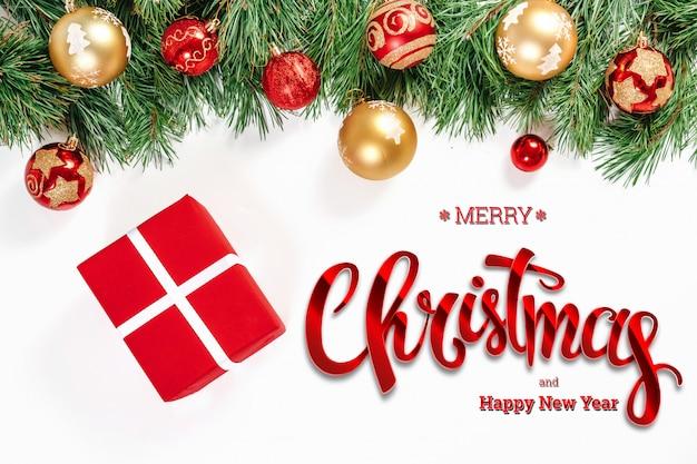 La inscripción de feliz navidad, abeto verde, juguetes y regalos en un blanco. tarjeta de navidad, fondo festivo. técnica mixta