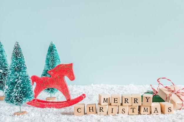 Inscripción de feliz navidad con abetos, juguete de caballo, cajas de regalo sobre fondo de nieve