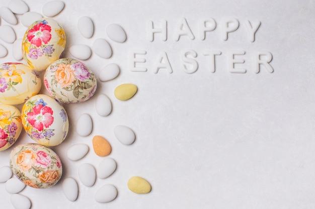 Inscripción feliz pascua con huevos decoupaged y grageas.