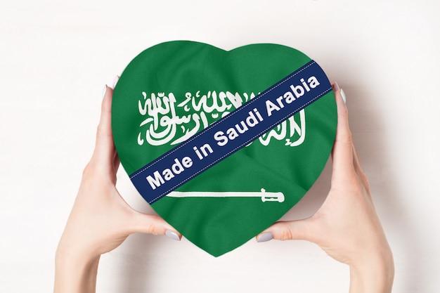 Inscripción hecha en arabia saudita la bandera de arabia saudita. manos femeninas que sostienen una caja en forma de corazón.