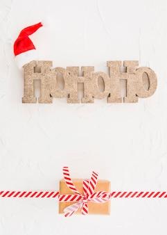Inscripción ho ho ho cerca de gorro navideño y caja de regalo.