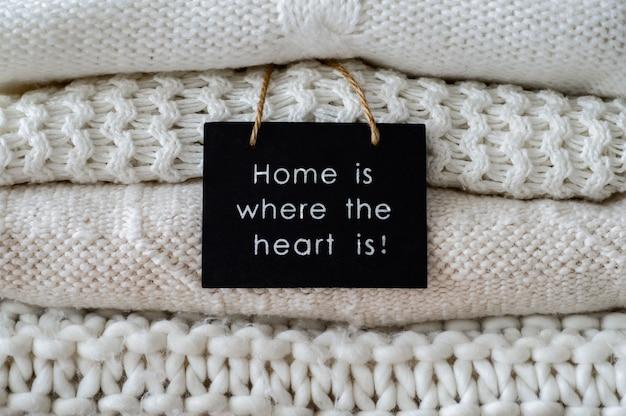 Inscripción hogar es donde está el corazón, con suéteres abrigados. montón de ropa de punto en tonos cálidos