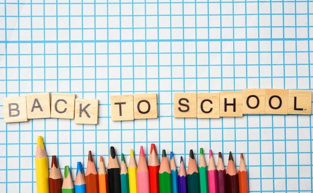 Inscripción de letras de madera de regreso a la escuela y lápices multicolores sobre un fondo de hoja blanca en una jaula, cerrar