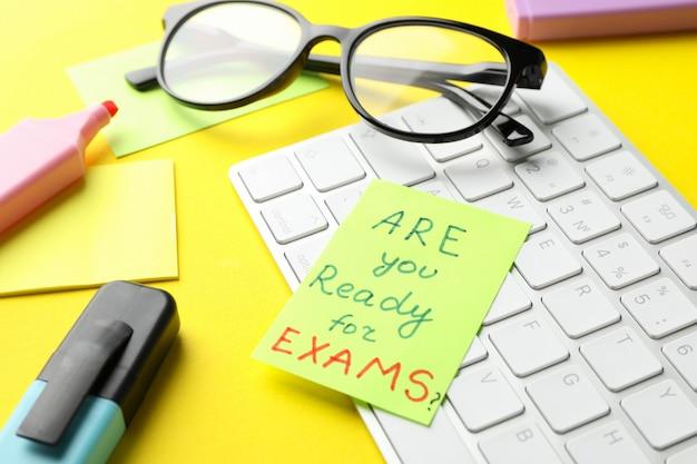 Inscripción ¿estás listo para los exámenes ?, teclado y estacionario sobre superficie amarilla, primer plano