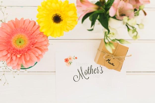Inscripción de madres con caja de regalo y gerberas.