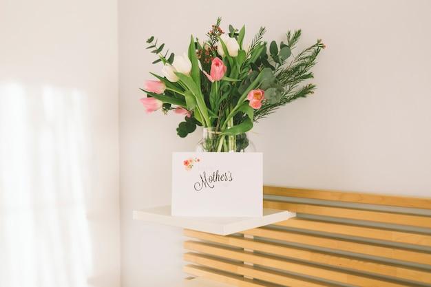 Inscripción de madres con flores en florero.