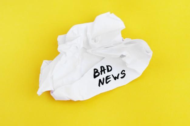 La inscripción malas noticias en papel arrugado sobre un fondo amarillo