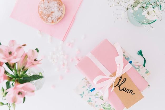 Inscripción de mamá con caja de regalo, flores y donut.