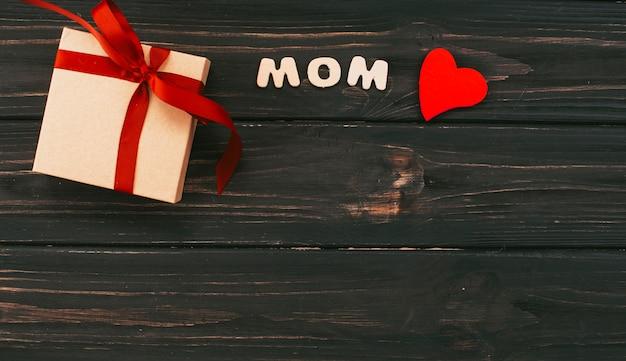 Inscripción de mamá con caja de regalo en mesa de madera.