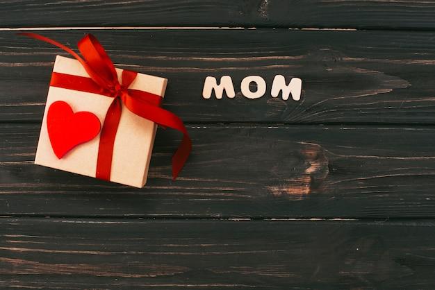 Inscripción de mamá con caja de regalo en mesa