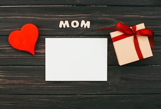 Inscripción de mamá con caja de regalo y papel sobre mesa