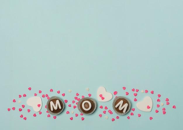 Inscripción de mamá en conjunto de caramelos entre decoraciones.