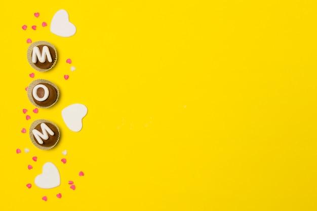 Inscripción de mamá en dulces caramelos entre decoraciones.