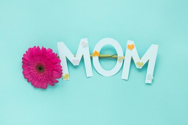 Inscripción de mamá con flor de gerbera en mesa