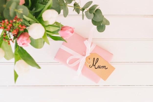 Inscripción de mamá con flores y caja de regalo.