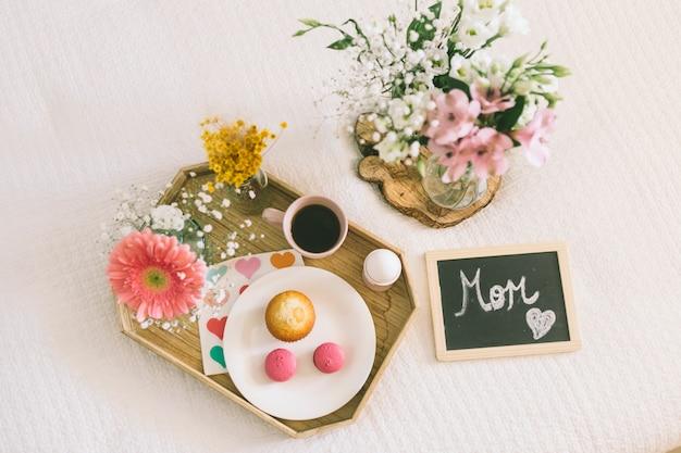 Inscripción de mamá con flores y macarrones en bandeja.