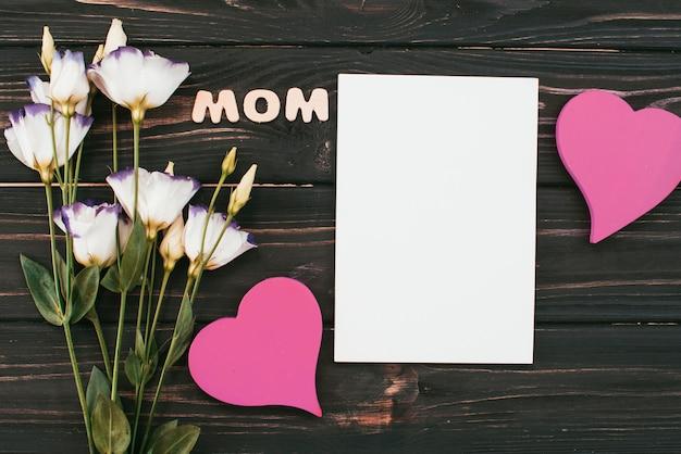 Inscripción de mamá con flores y papel en blanco.