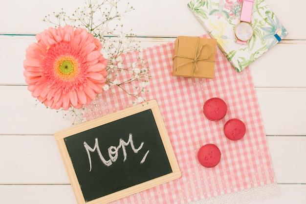Inscripción de mamá con gerbera y regalo.