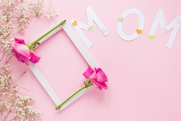 Inscripción de mamá con marco y rosas en mesa
