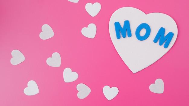 Inscripción de mamá con pequeños corazones de papel en mesa