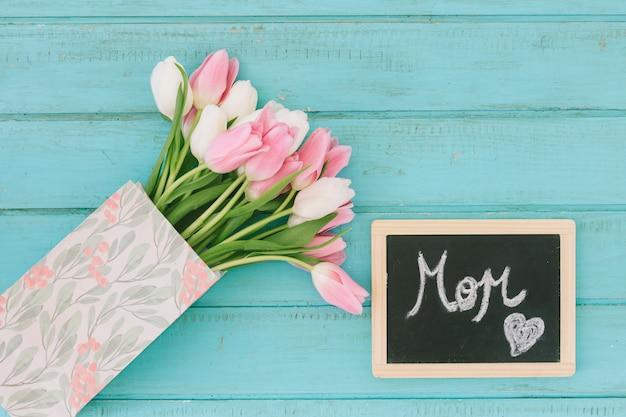 Inscripción de mamá en pizarra con ramo de tulipanes