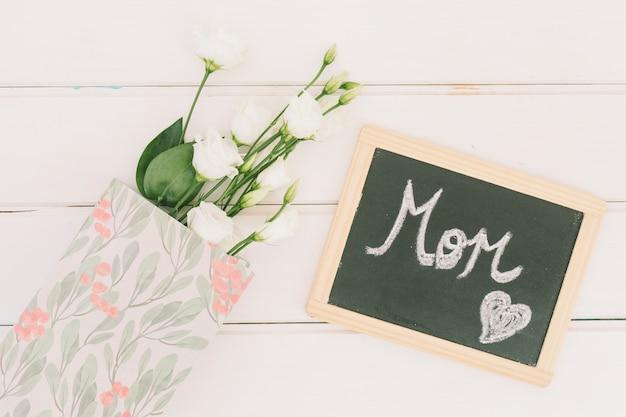 Inscripción de mamá en pizarra con rosas