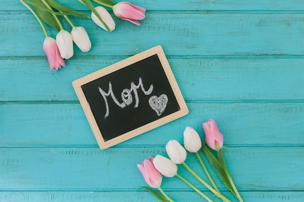 Inscripción de mamá en pizarra con tulipanes