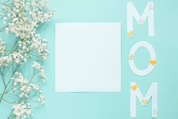 Inscripción de mamá con ramas de flores y hoja de papel.