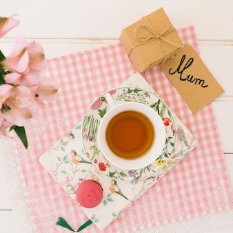 Inscripción de mamá con taza de té y regalo.