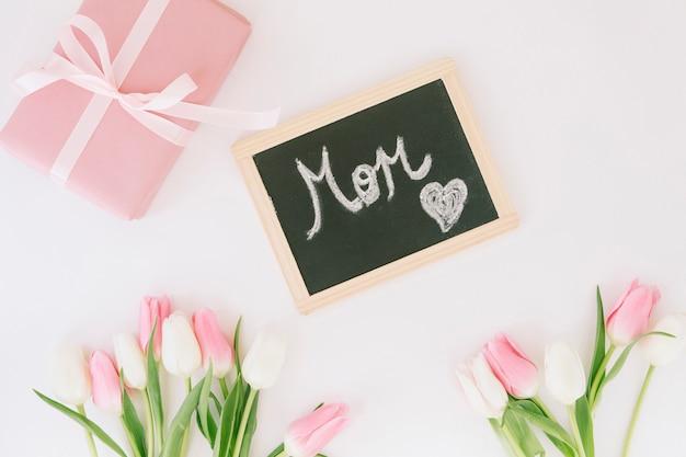 Inscripción de mamá con tulipanes y regalo.