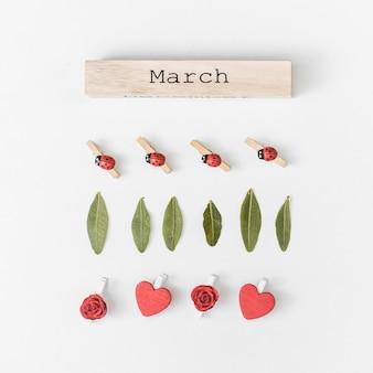 Inscripción de marzo con hojas verdes y flores.