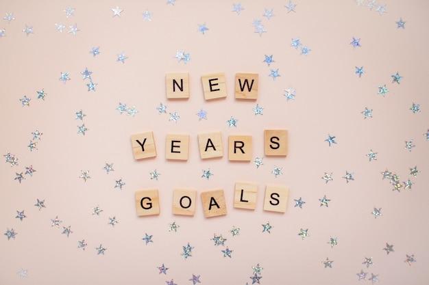 La inscripción metas de año nuevo de bloques de madera con estrellas plateadas.