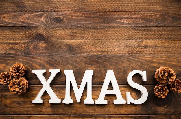 Inscripción de navidad cerca de ganchos en tablero de madera