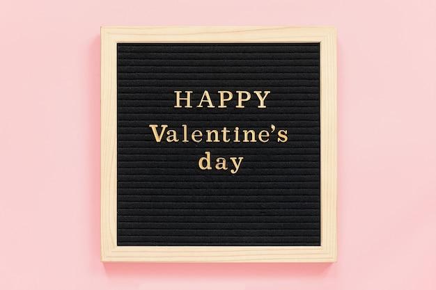 Inscripción de oro feliz día de san valentín en pizarra negra, composición central sobre fondo rosa.