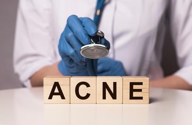 Inscripción de palabra acné en papel en manos del médico