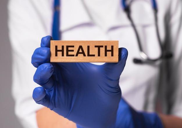 Inscripción de palabra salud en manos del médico en guante