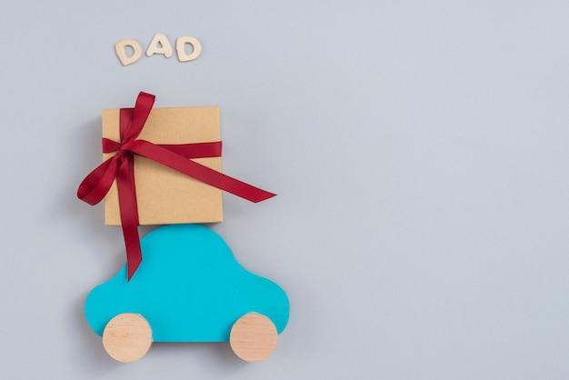 Inscripción de papá con caja de regalo y carro pequeño.