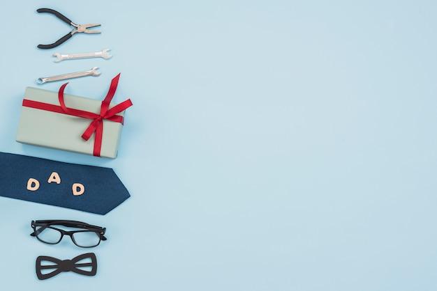 Inscripción de papá con caja de regalo, herramientas y corbata.