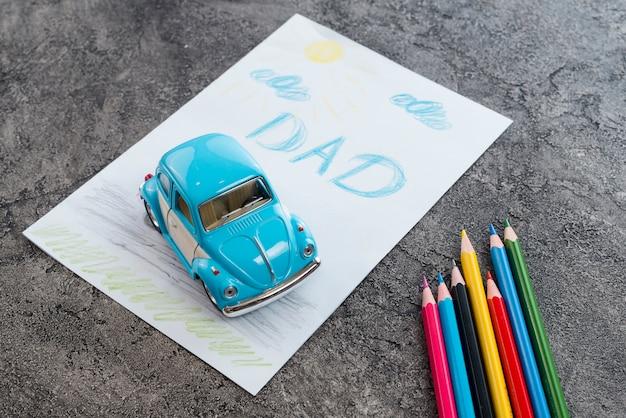 Inscripción de papá con coche de juguete y lápices.